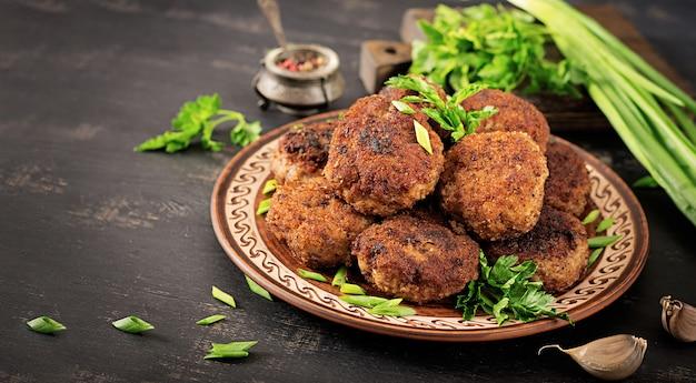 Juteuses côtelettes de viande délicieuses sur une table sombre Photo Premium