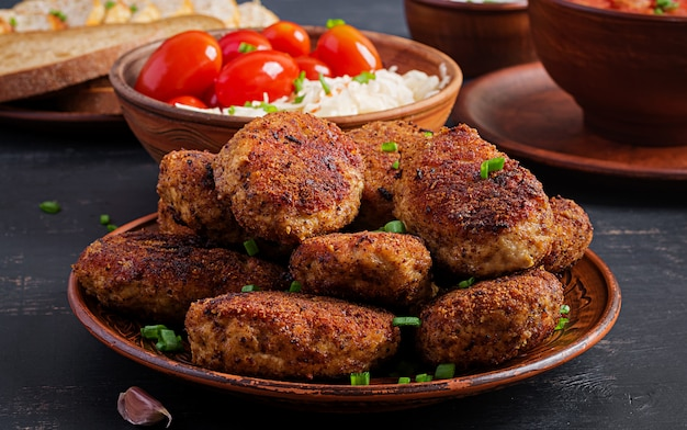 Juteuses côtelettes de viande délicieuses sur une table sombre. Photo Premium