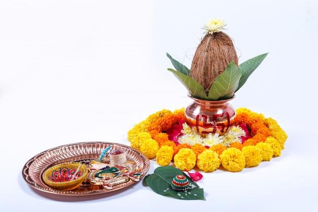 Kalash en cuivre avec noix de coco, feuille et décoration florale sur fond blanc Photo Premium