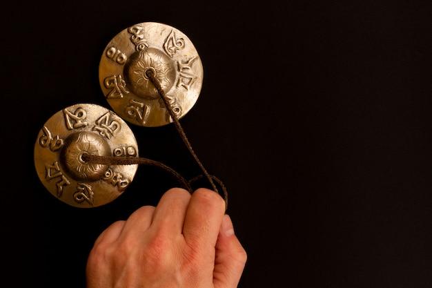 Karatals en or cymbales tibétain tingsha pour la méditation est dans la main de l'homme Photo Premium
