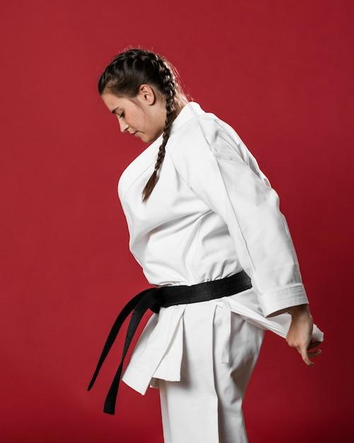 Karaté Femme En Kimono Blanc Traditionnel Sur Fond Rouge Photo gratuit