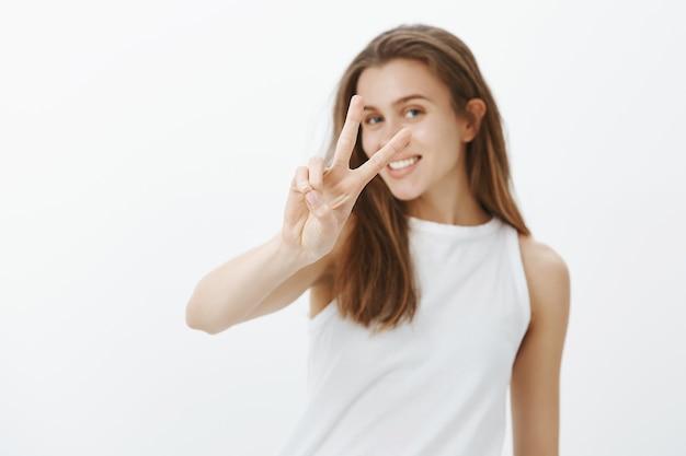 Kawaii Jeune Femme Caucasienne Montrant Le Geste De Paix Et Souriant Avec Des Dents Blanches Photo gratuit