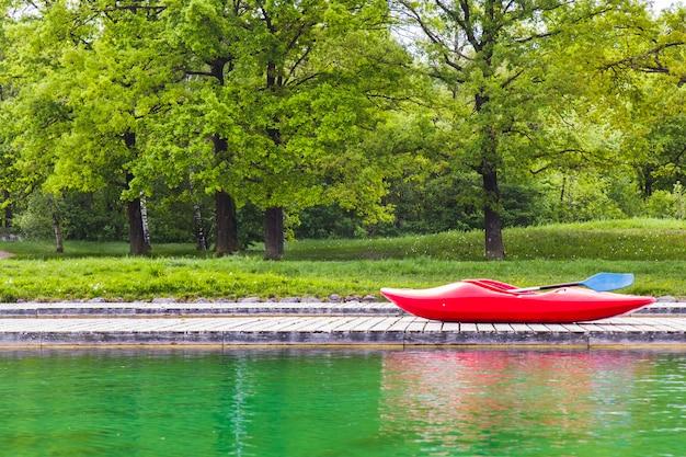 Un kayak rouge sur une jetée en bois dans un lac Photo Premium