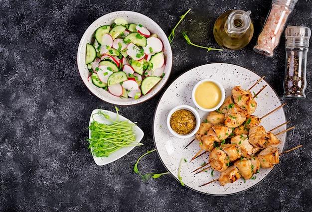 Kebab de poulet grillé et salade au concombre, radis, oignon à la noirceur. Photo Premium