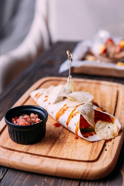 Kebab de viande avec des frites garnies de sauce et servi avec une salade de tomates sur une assiette en bois Photo Premium