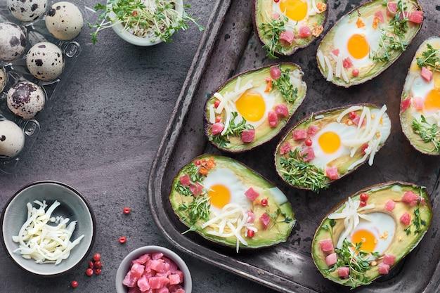 Keto diet diet: barques d'avocats avec cubes de jambon, œufs de caille, fromages et germes de cresson Photo Premium