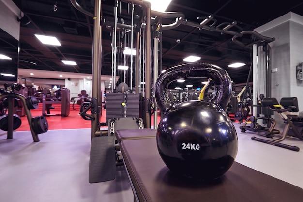 Kettlebell sur fond d'un simulateur dans la salle de gym. intérieur Photo Premium