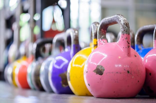Kettlebells colorés dans une rangée dans un gymnase Photo Premium
