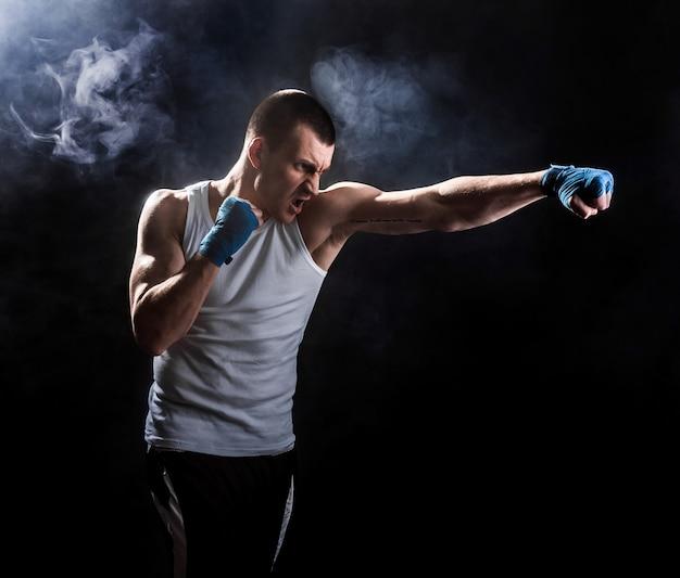 Kickbox musculaire ou muay thai combattant poing dans la fumée Photo Premium