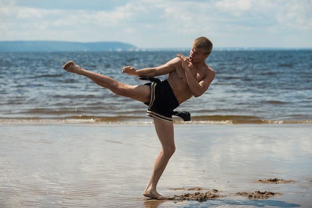 Kickboxer donne un coup de pied en plein air en été contre la mer. Photo Premium