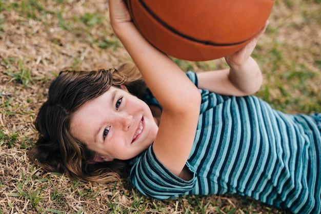 Kid couché sur l'herbe et tenir le ballon Photo gratuit