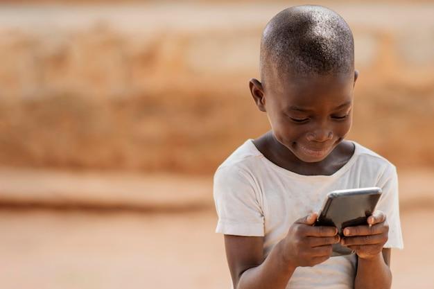 Kid Coup Moyen Tenant Un Smartphone Photo gratuit