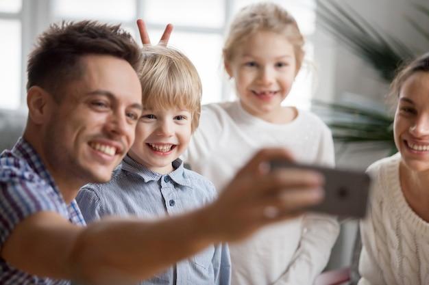 Kid fille faisant des oreilles de lapin frère pendant que le père prend selfie Photo gratuit