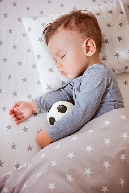 Kid, le garçon dort dans un berceau embrassant un ballon de foot Photo Premium