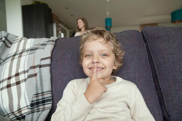 Kid garçon tenant un doigt sur les lèvres en jouant à cache-cache Photo gratuit