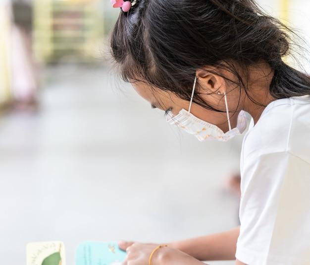 Kid girl avec masque de protection à l'école Photo Premium