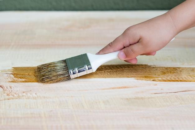 Kid hand varnishing une étagère en bois à l'aide d'un pinceau Photo gratuit