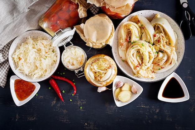 Kimchi au chou, bocaux en verre aigre mariné avec tomates marinées et choucroute Photo Premium