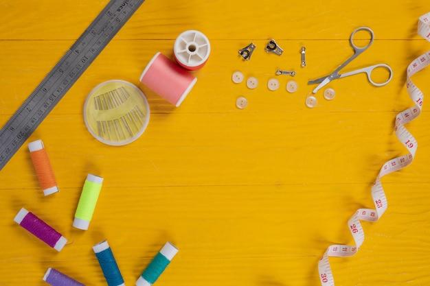 Un kit de couture, une aiguille, du fil, une aiguille, placés sur un plancher en bois jaune. Photo gratuit