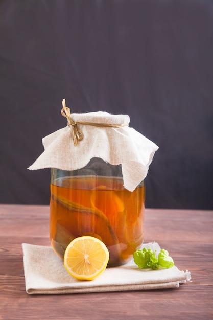 Kombucha Dans Un Bocal En Verre, Citron Et Une Feuille De Menthe Sur Une Table En Bois. Boisson Fermentée. Concept De Nourriture Saine. Photo Premium