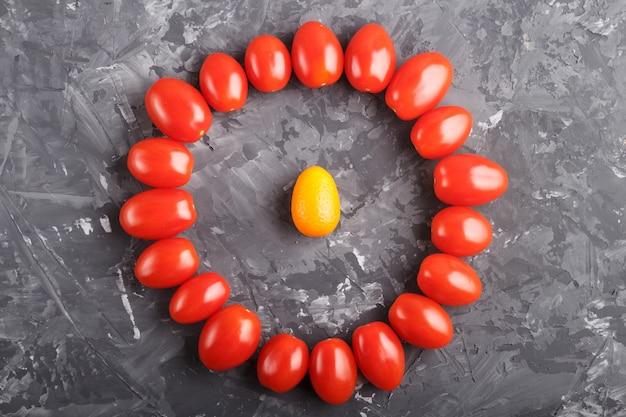 Un kumquat dans un cercle de tomates cerises sur fond noir Photo Premium