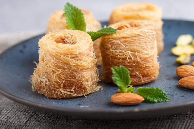 Kunafa, bonbons arabes traditionnels en plaque de céramique bleue sur un béton gris. fermer. Photo Premium