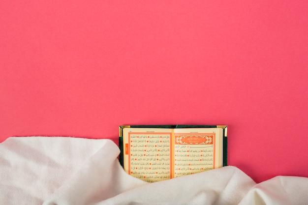 Un kuran islamique ouvert avec un chiffon blanc sur fond rouge Photo gratuit