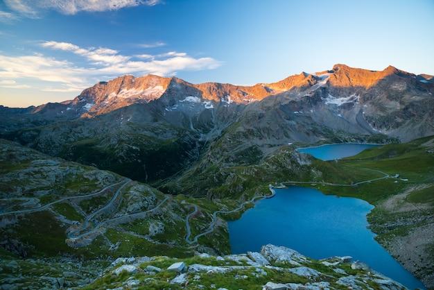 Lac alpin d'altitude, barrages et bassins d'eau sur des terres idylliques avec des sommets de montagnes rocheuses majestueuses qui brillent au coucher du soleil Photo Premium