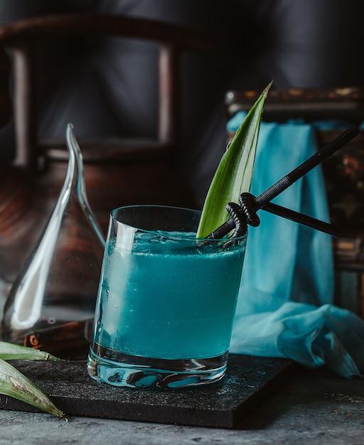Lagon bleu dans un verre avec feuille d'ananas et pailles noires Photo gratuit