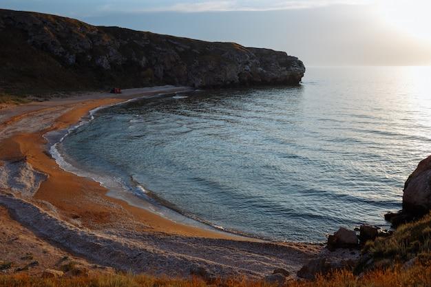 Lagune de mer avec une plage de sable et une tente au coucher du soleil Photo Premium
