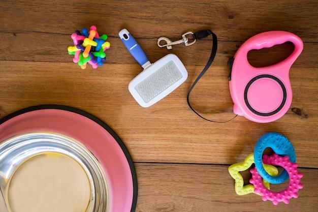 Laisses pour animaux de compagnie et jouets en caoutchouc sur fond en bois. Photo Premium