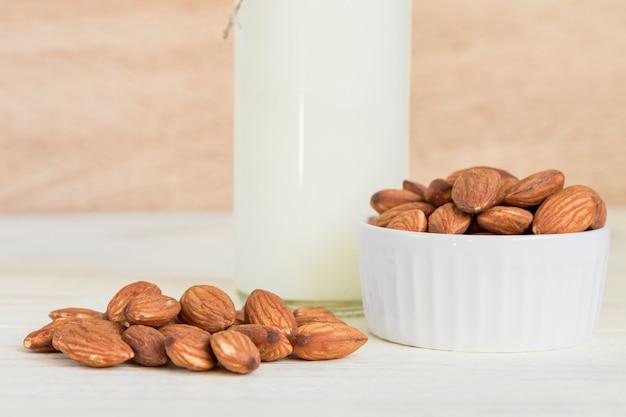 Lait d'amande fait maison dans une bouteille et les noix dans un bol en porcelaine blanche sur fond en bois Photo Premium
