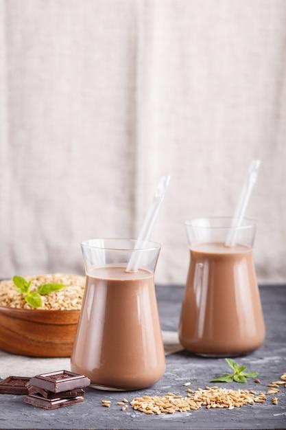 Lait Au Chocolat D'avoine Non Laitier Biologique En Verre Et Assiette En Bois Avec Des Graines D'avoine Sur Un Fond De Béton Noir Photo Premium
