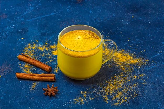 Lait De Curcuma Indien Traditionnel Dans Une Tasse En Verre Avec étoile D'anis Et Cannelle Photo Premium