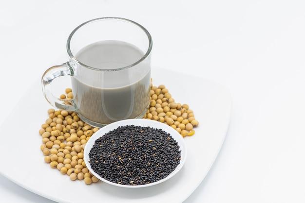 Lait de soja au sésame noir en verre sur fond blanc. Photo Premium