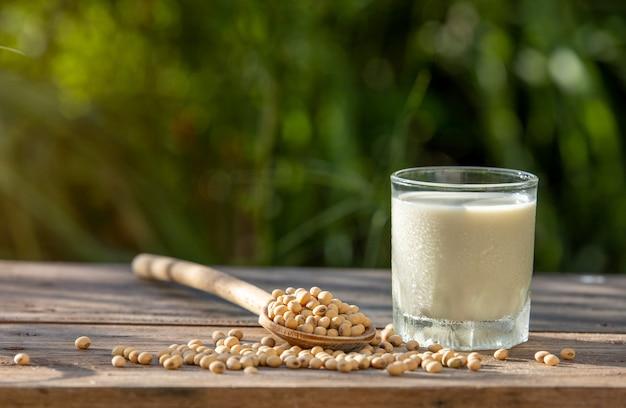 Lait de soja frais et soja sur table en bois avec éclairage le matin Photo Premium