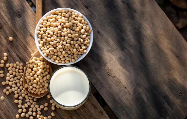 Lait de soja et soja sur une table en bois avec éclairage le matin Photo Premium