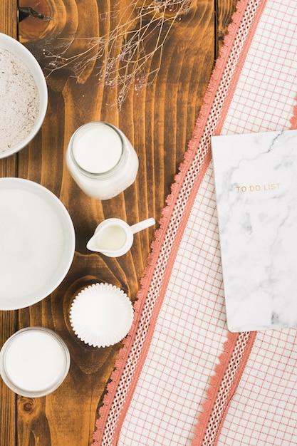 Lait; sucre; moule à farine et à gâteaux avec une liste de choses à faire sur un tissu texturé sur une table texturée en bois Photo gratuit