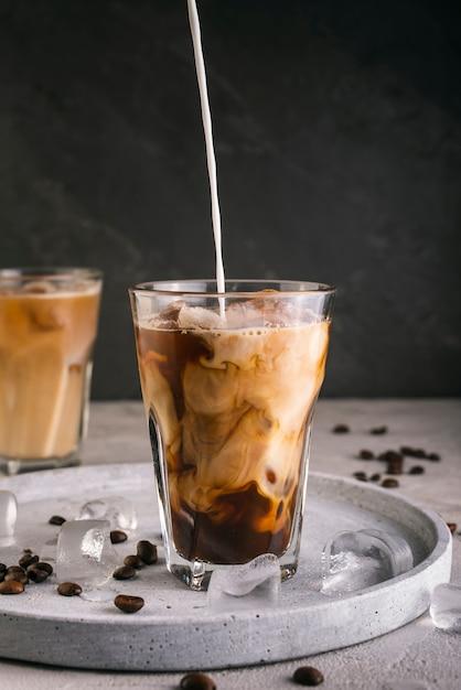 Lait Verser Dans Le Verre à Café Photo gratuit