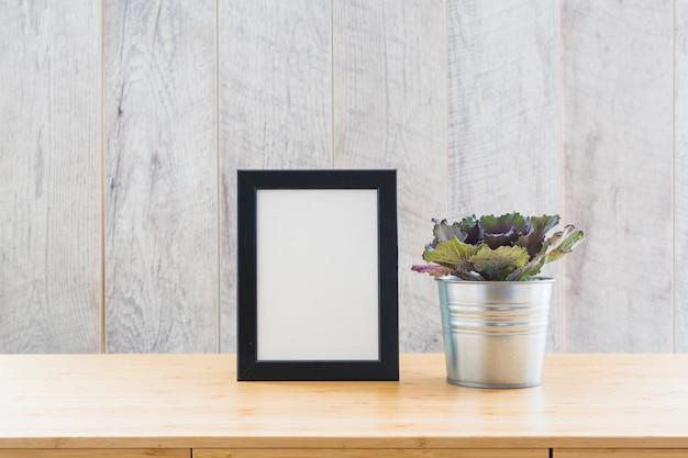 Laitue feuille de chêne rouge en pot avec un cadre d'image vide sur la table Photo gratuit