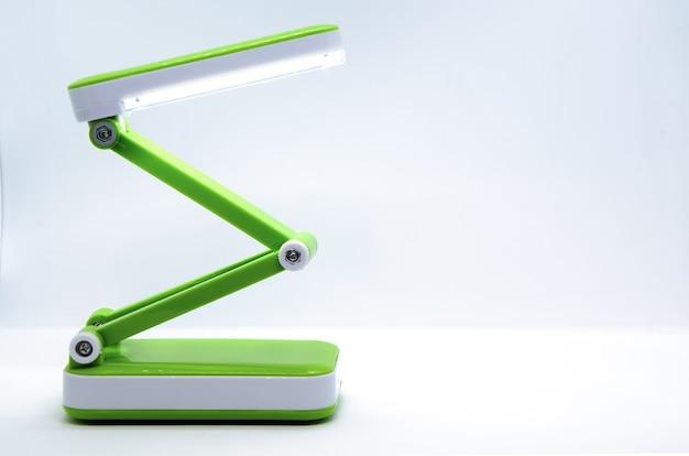 Lampe De Bureau Led Portable Pliable Et Compacte Avec Corps Flexible En Plastique Vert Brillant Sur Fond Blanc. Photo Premium
