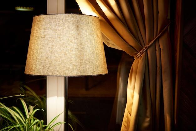 Lampe classique avec faible éclairage près de la fenêtre. Photo Premium