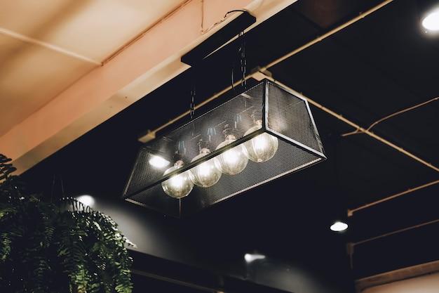 Lampe led vintage edison ou ampoule à incandescence au restaurant ou café avec tons marron et orange. Photo Premium
