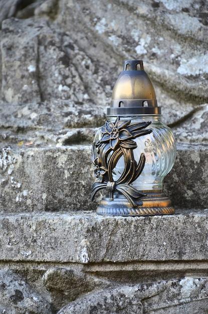 Une lampe en métal se dresse sur la surface de pierre d'une ancienne crypte Photo Premium