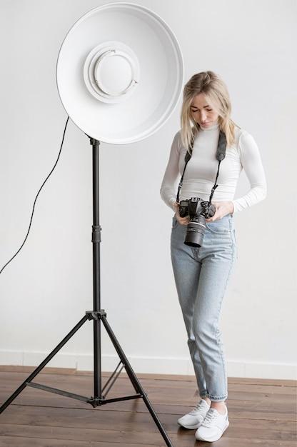 Lampe De Studio Et Femme Tenant Un Appareil Photo Photo gratuit