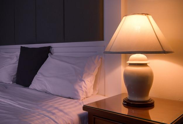 Lampe sur une table de nuit à côté d'un lit classique. Photo Premium