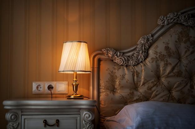 Lampe sur une table de nuit à côté d'un lit Photo Premium