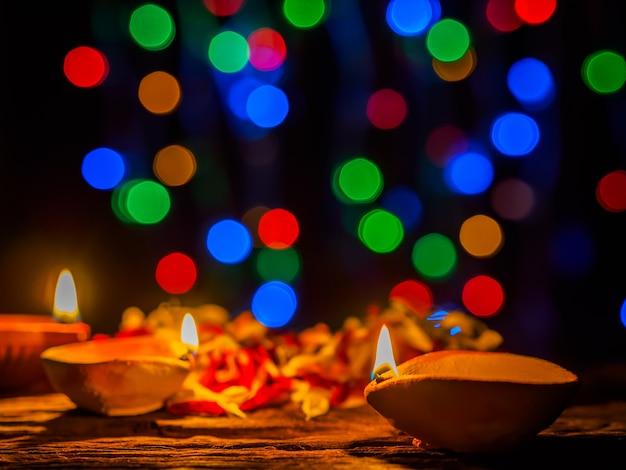 Lampes diya éclairées par un fond de bokeh lors d'une célébration diwali Photo Premium