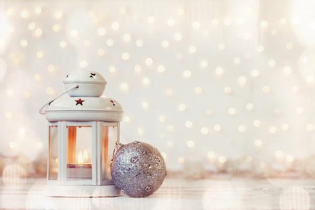 Lanterne blanche avec bougie et boule en argent - décoration de noël. Photo Premium