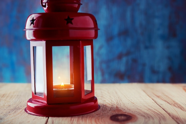 Lanterne avec une bougie allumée à l'intérieur sur une table en bois sur une sombre Photo Premium